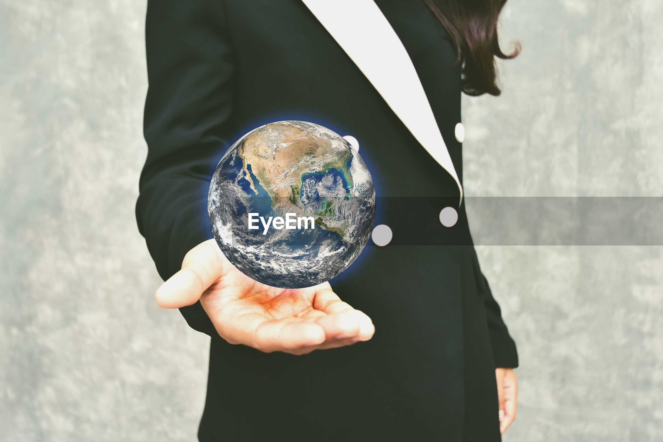 Digital composite image of woman holding earth