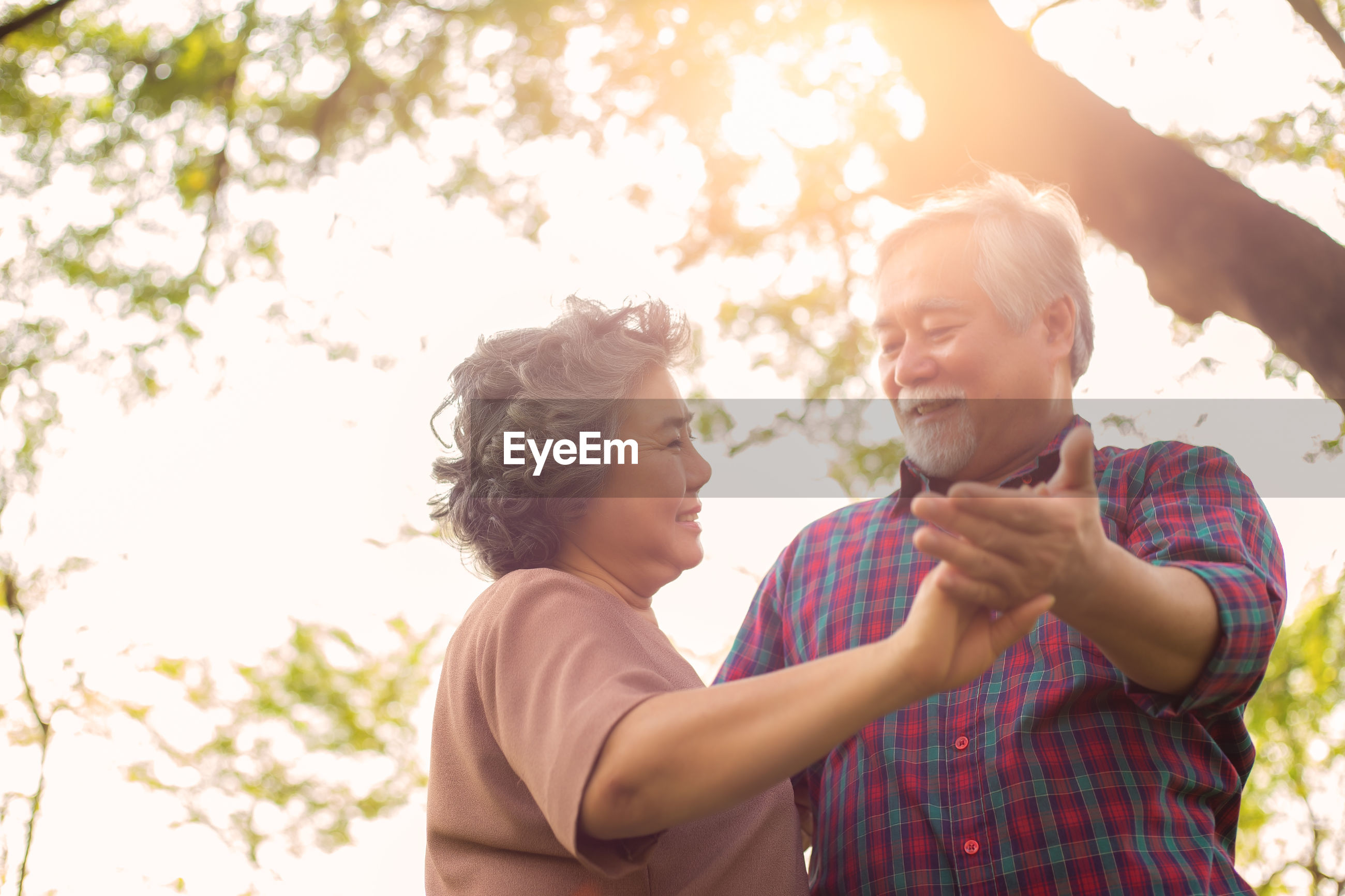 Smiling senior couple dancing against trees