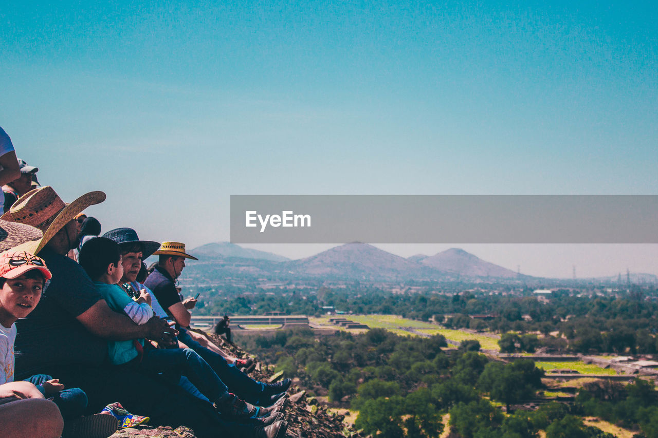 HIGH ANGLE VIEW OF PEOPLE SITTING ON LANDSCAPE AGAINST MOUNTAINS