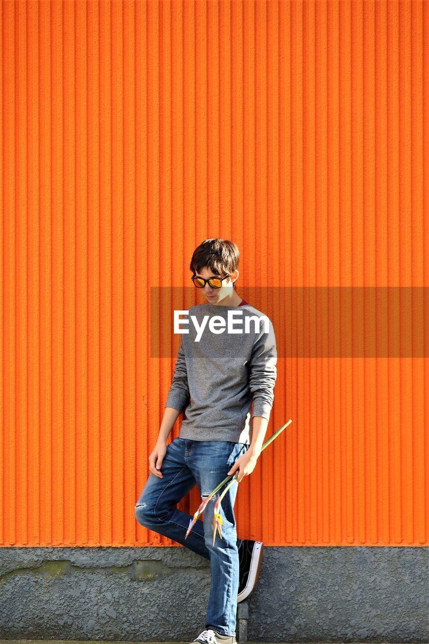 Teenage boy standing by orange wall