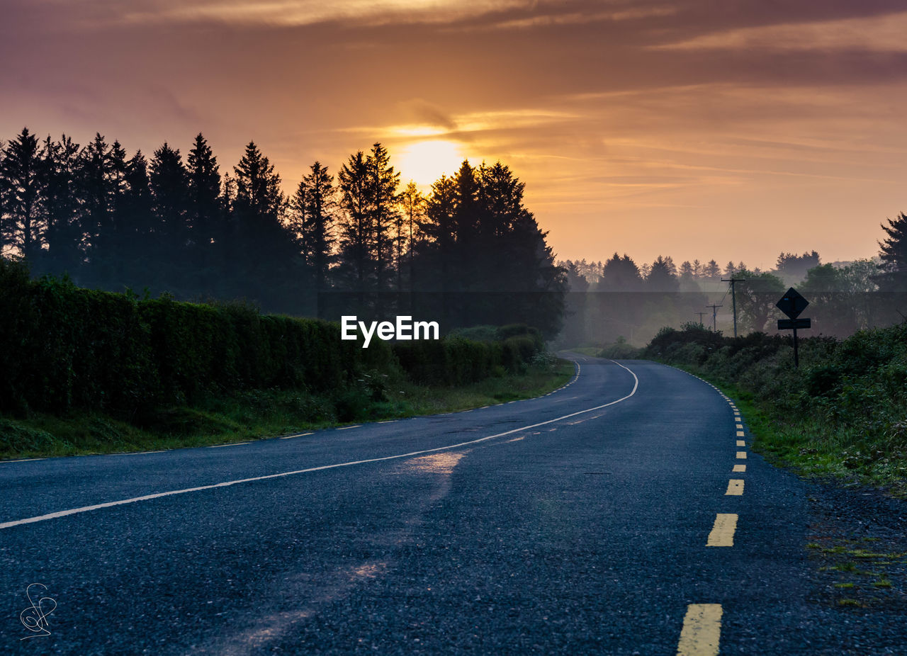 road, the way forward, tree, road marking, transportation, sunset, diminishing perspective, empty, no people, scenics, sky, tranquil scene, nature, beauty in nature, landscape, tranquility, outdoors, road sign, day