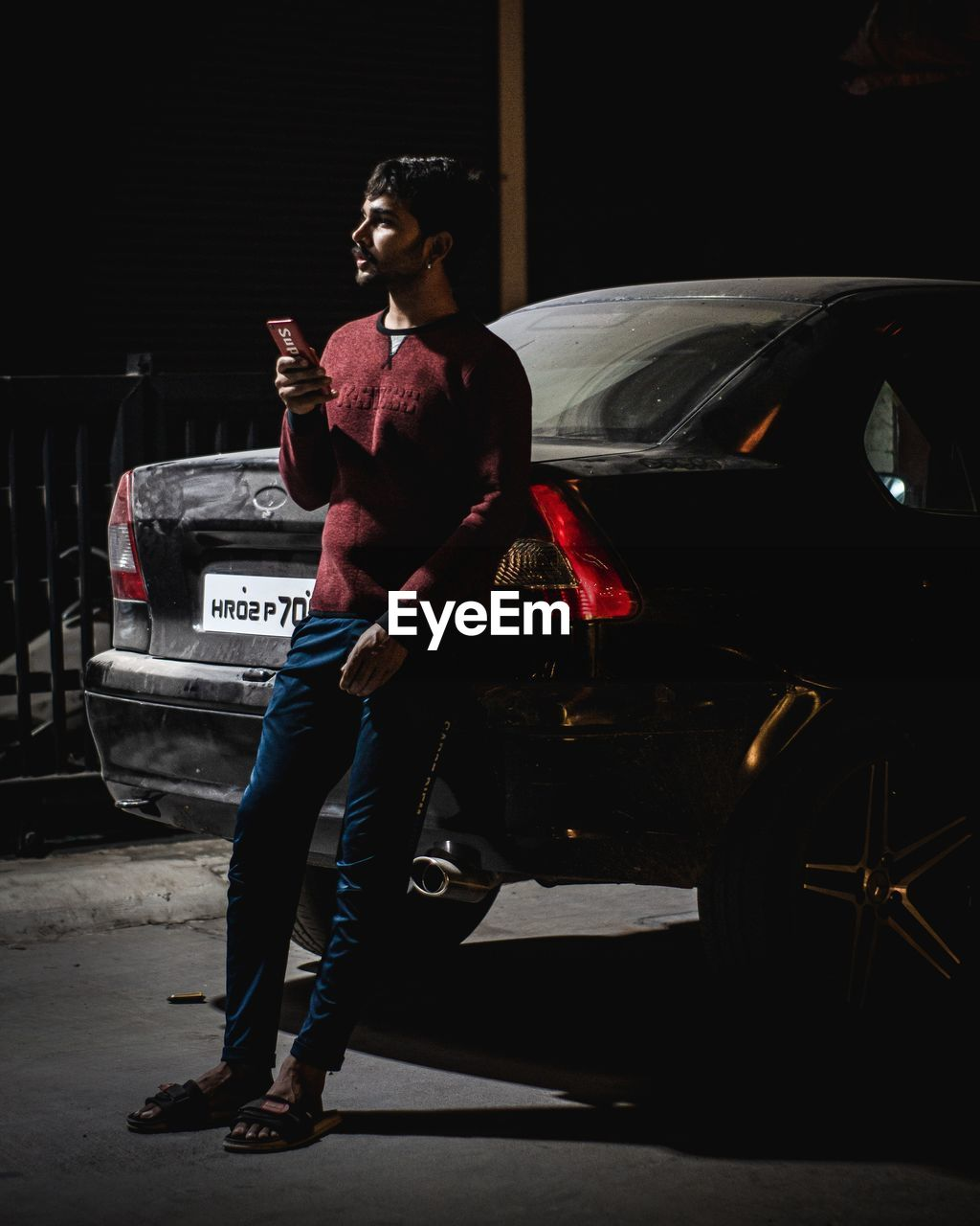 FULL LENGTH OF YOUNG MAN LOOKING AWAY WHILE HOLDING CAR