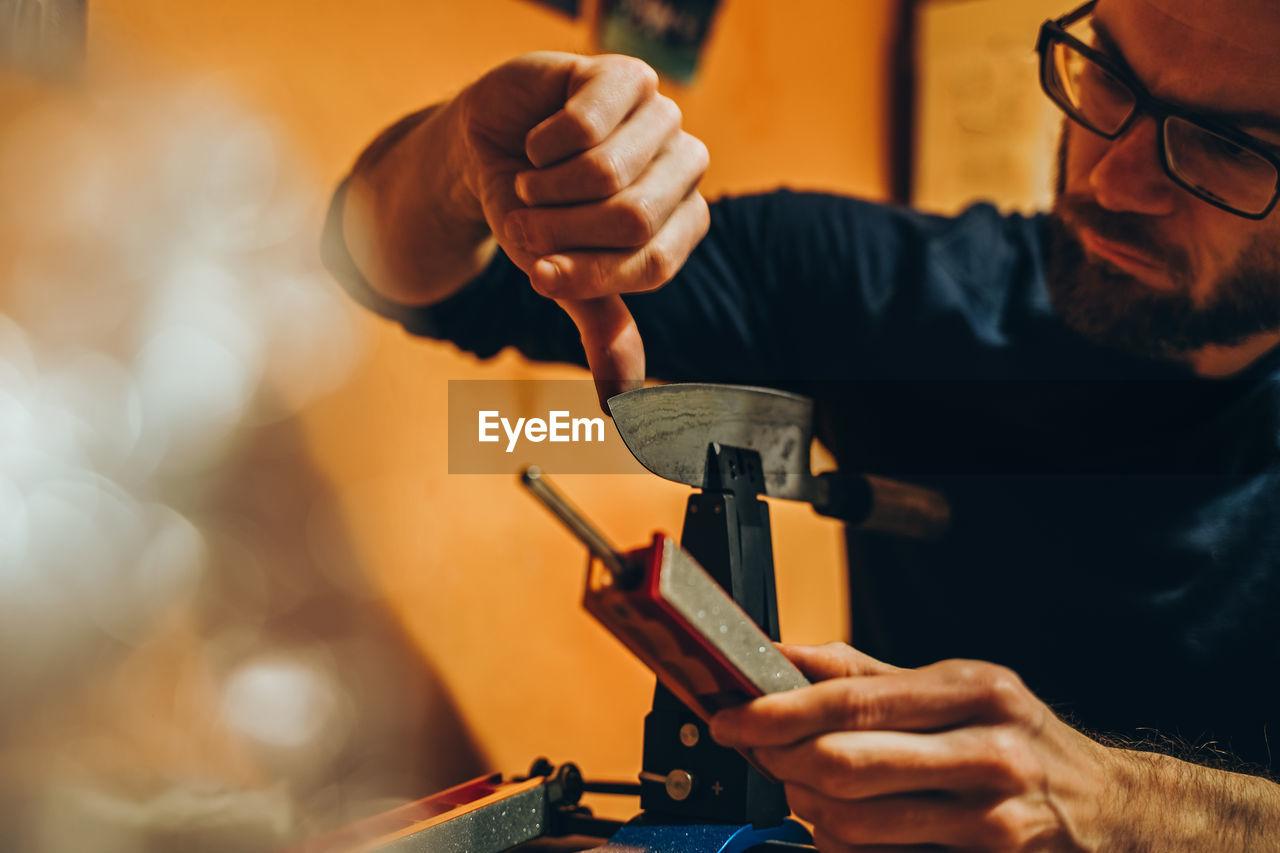 Man checking sharp knife machine in workshop