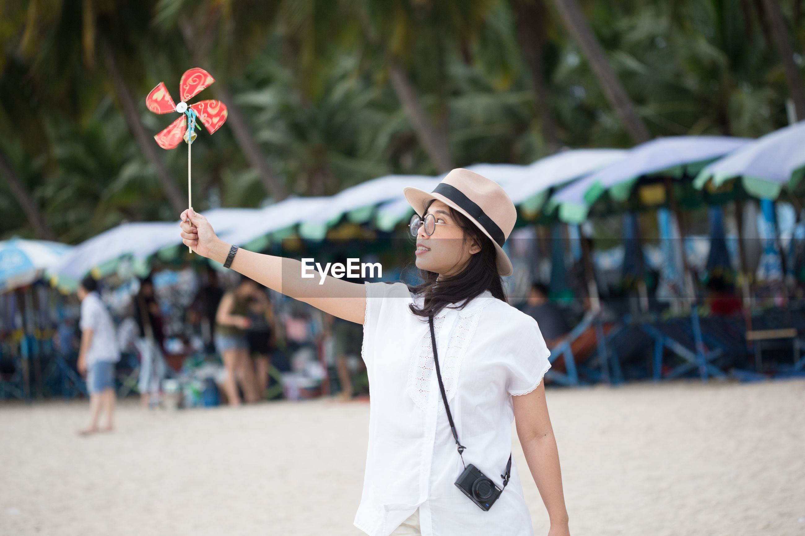 Woman holding pinwheel toy while standing on beach