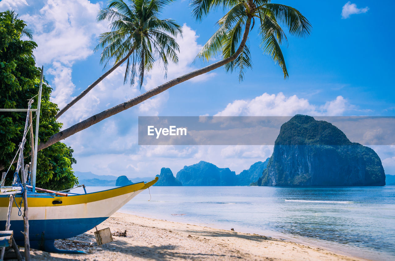 water, sky, sea, nautical vessel, beach, transportation, tree, beauty in nature, cloud - sky, land, mode of transportation, scenics - nature, tranquility, nature, palm tree, tropical climate, plant, day, tranquil scene, no people, outdoors, coconut palm tree
