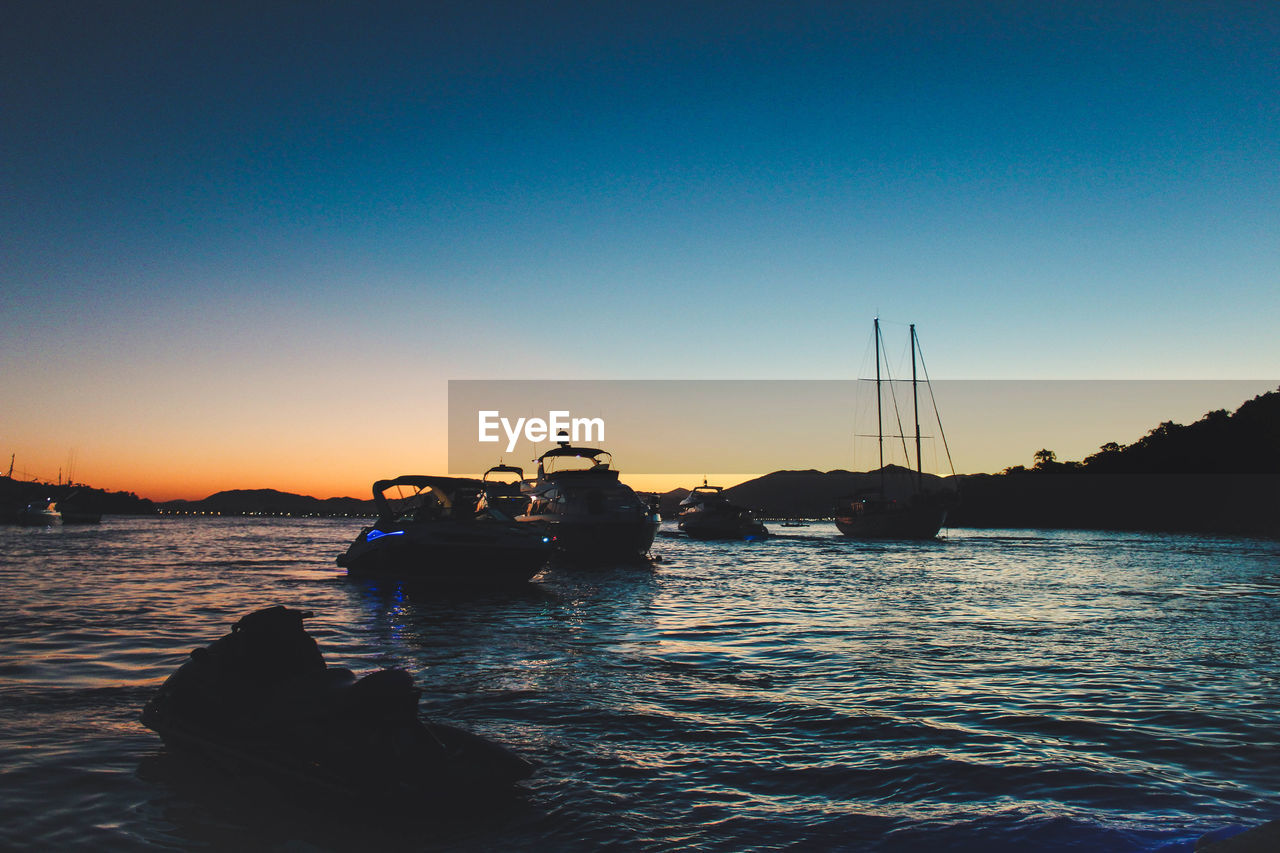nautical vessel, water, transportation, sunset, mode of transport, sea, nature, boat, beauty in nature, clear sky, outdoors, rippled, scenics, silhouette, sky, tranquility, waterfront, blue, sailing, no people, mountain, day