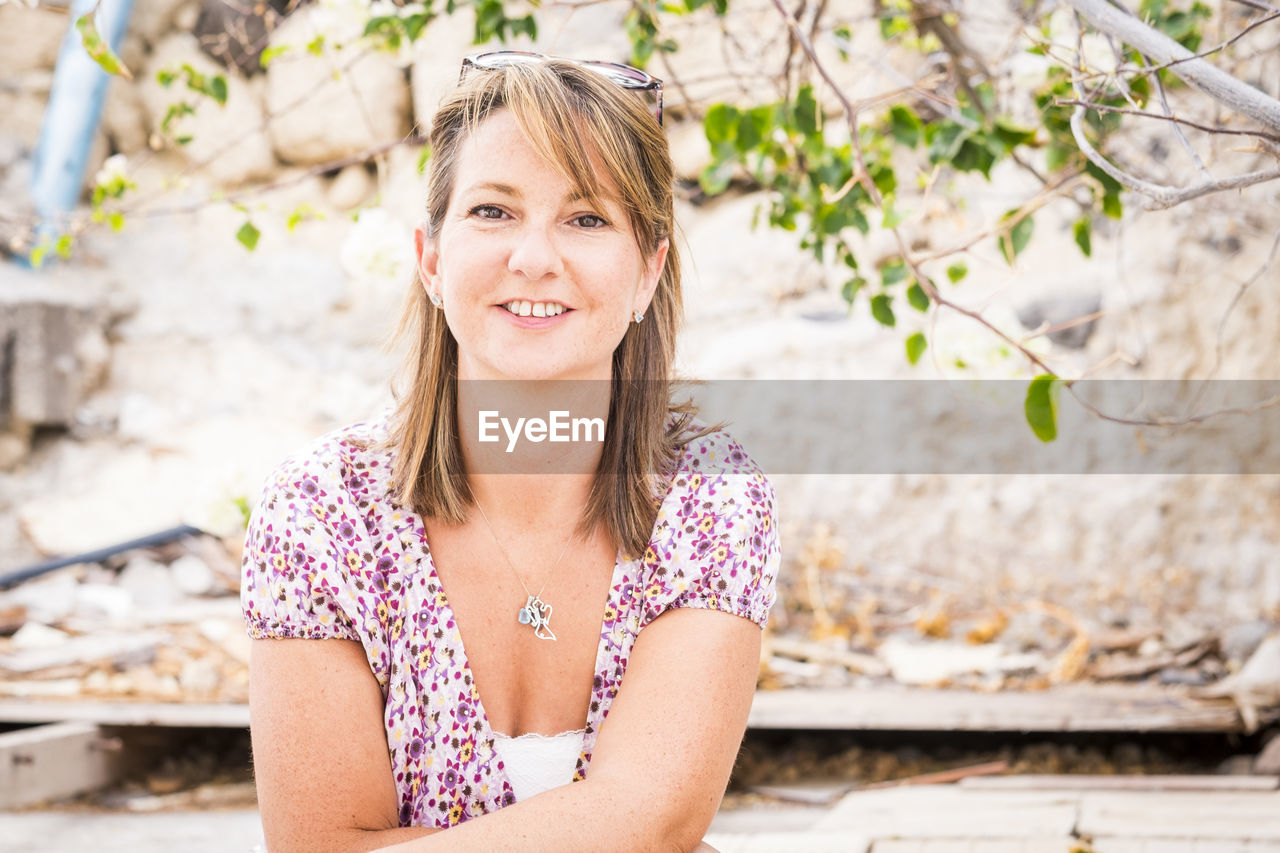 Portrait of smiling mature woman sitting against rock formation