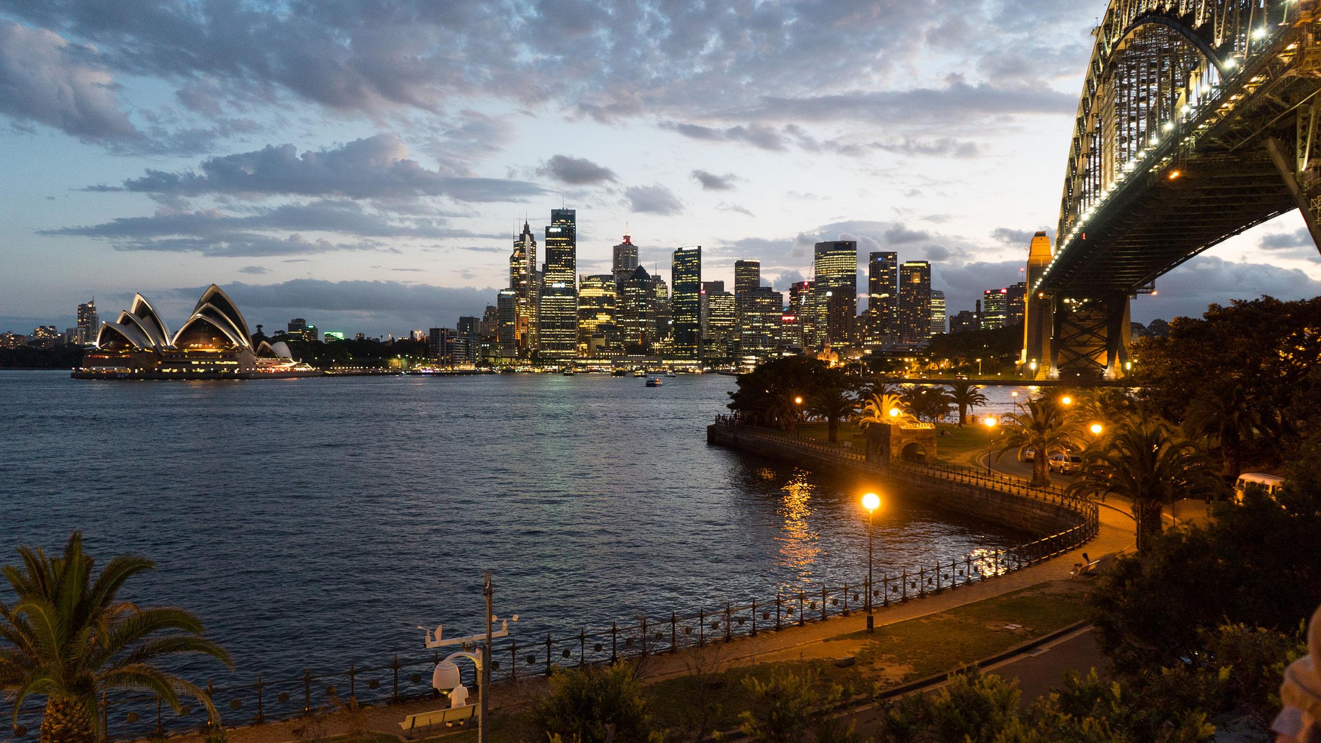 Illuminated sydney harbor bridge over sea by opera house and city skyline against sky