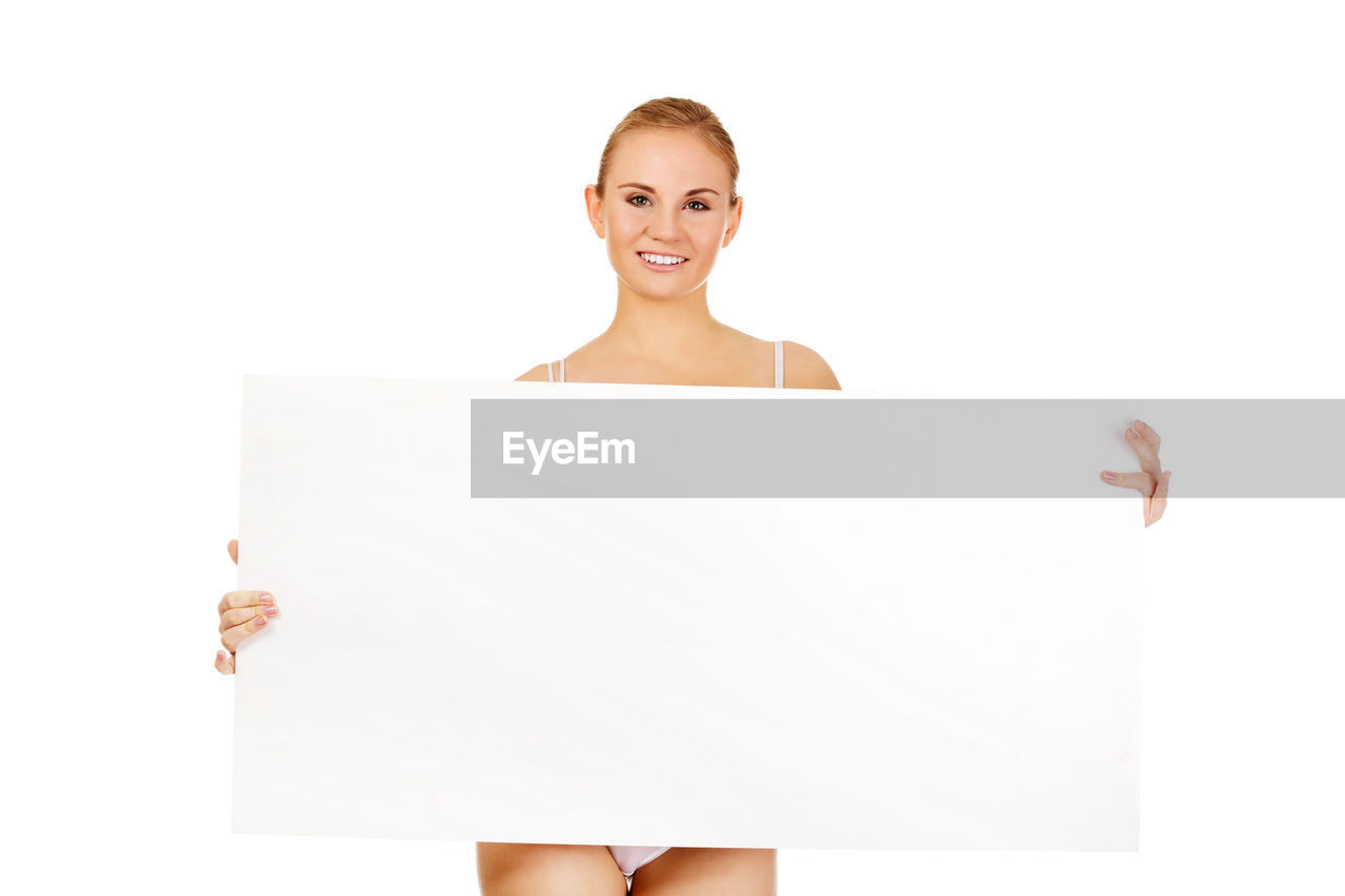 Portrait Of Young Woman Holding Blank Placard While Standing Against White Background