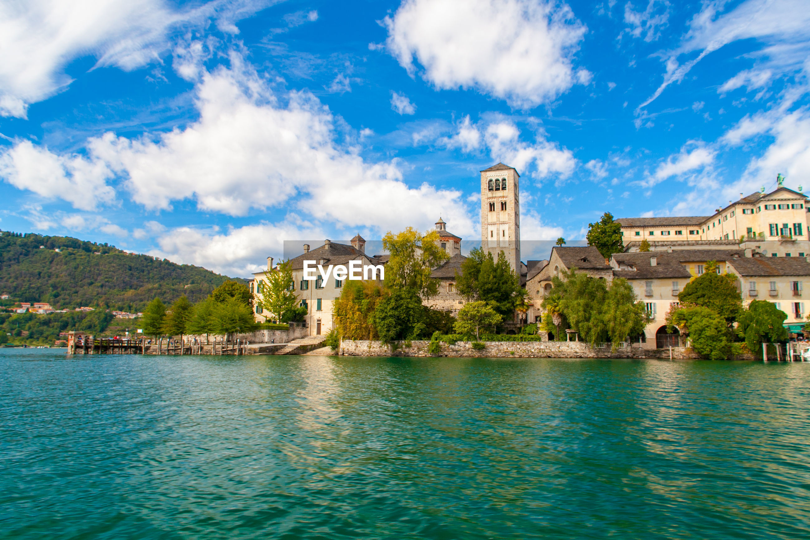 Isola san giulio inside orta's lake, piemonte, italy, from water surface with blue sky.