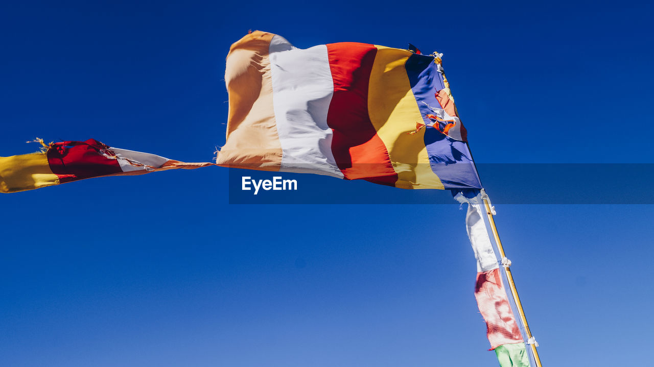 Low Angle View Of Flag Against Clear Blue Sky On Sunny Day