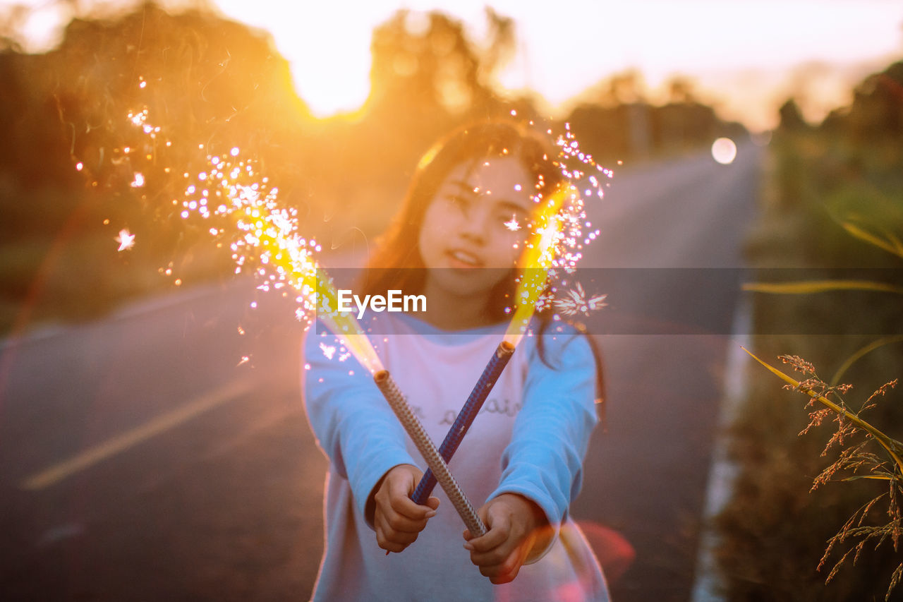 Portrait of teenage girl holding fireworks on road