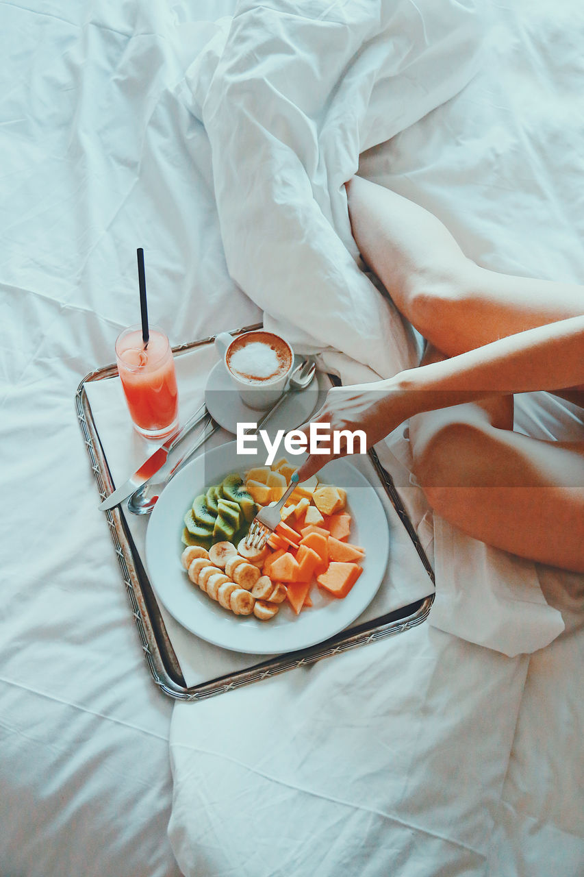 Midsection Of Woman Having Breakfast On Bed