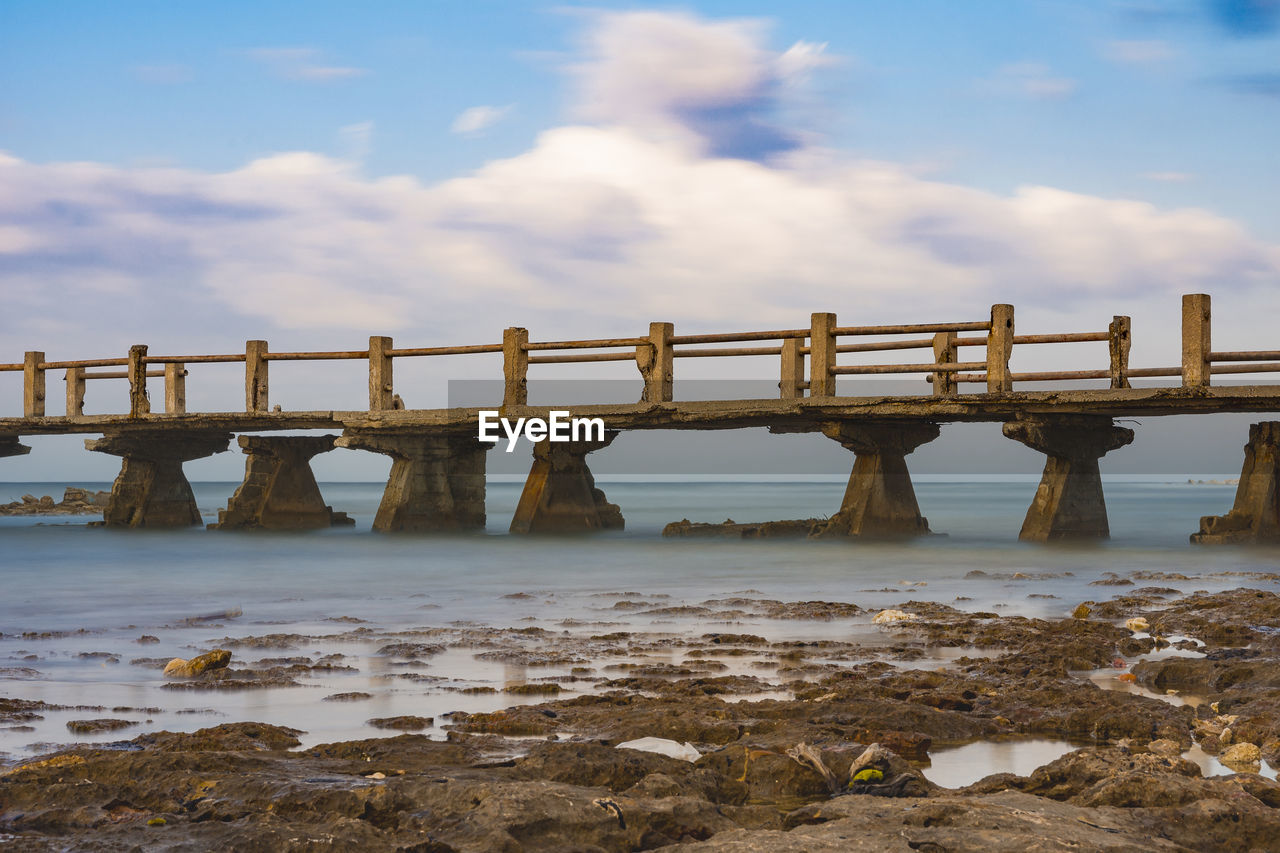 water, sky, cloud - sky, nature, scenics - nature, sea, day, land, tranquility, beach, no people, beauty in nature, tranquil scene, solid, outdoors, non-urban scene, rock, connection, wood - material, wooden post
