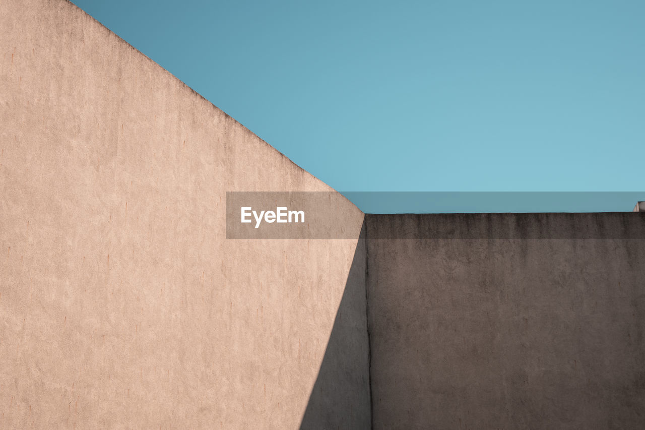 architecture, copy space, wall - building feature, built structure, sky, no people, building exterior, blue, clear sky, day, nature, low angle view, sunlight, wall, outdoors, brown, building, surrounding wall, pattern, close-up