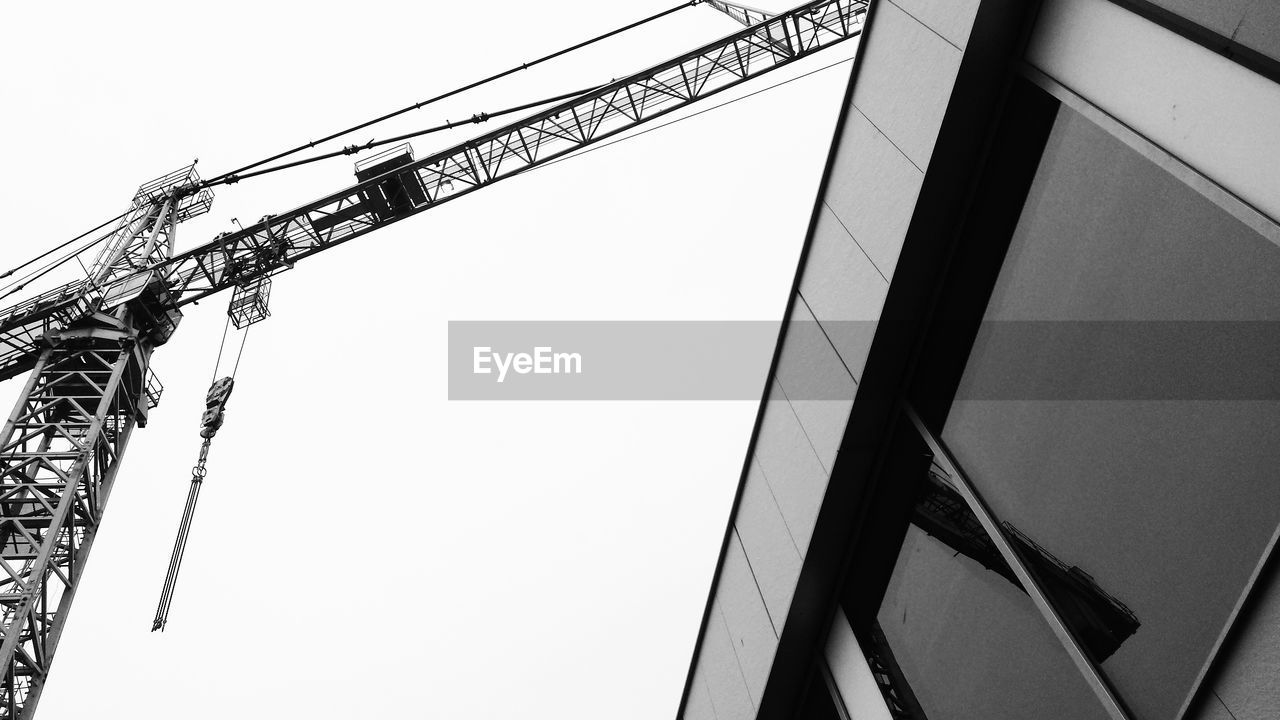 Low angle view of building and crane against clear sky