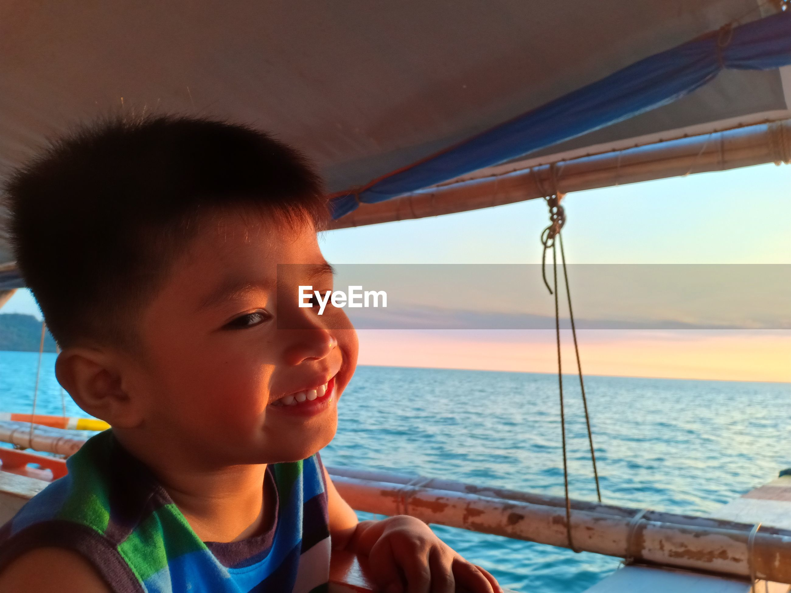 Portrait of smiling boy on boat in sea against sky