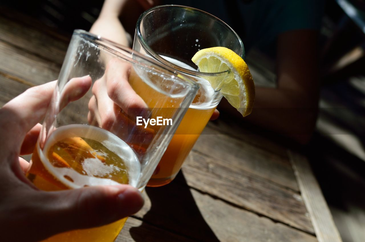 Cropped Image Of Hand Toasting Beer Glasses At Table