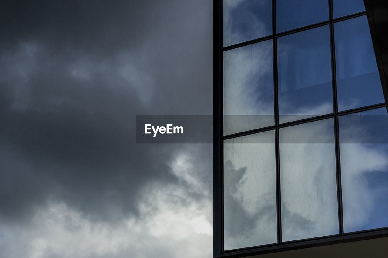 cloud - sky, sky, low angle view, nature, no people, glass - material, overcast, storm, window, storm cloud, outdoors, day, beauty in nature, architecture, building exterior, cloudscape, built structure, transparent, shape, ominous