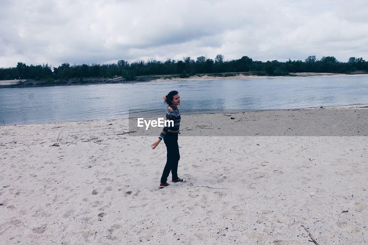 Woman Walking At Beach Against Sky