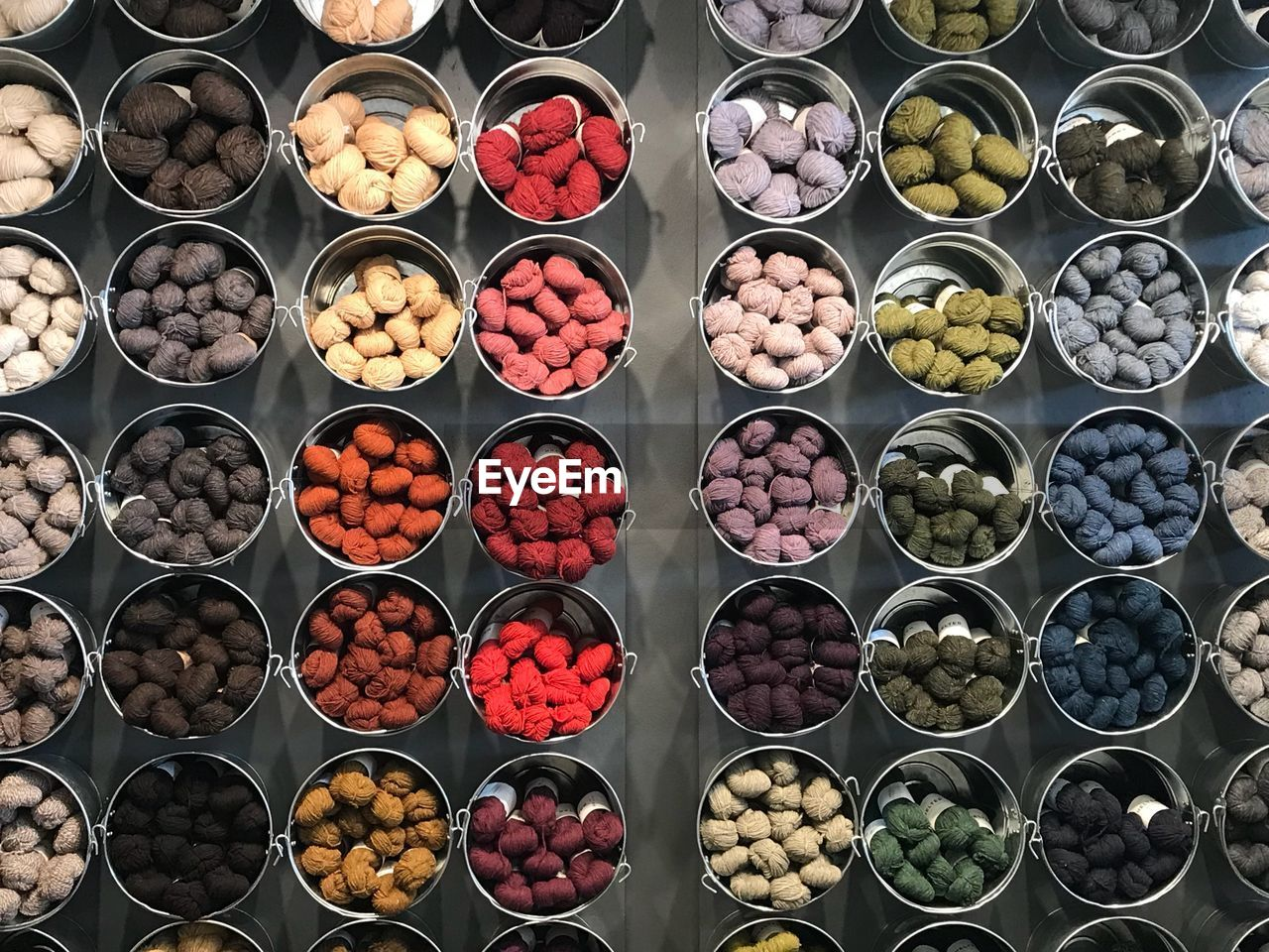 High angle view of colorful wools in buckets for sale in market