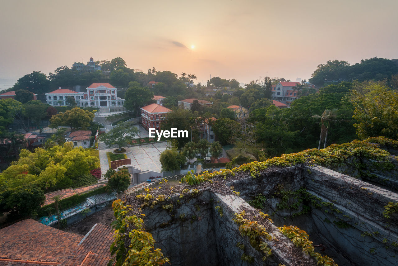HIGH ANGLE VIEW OF TOWNSCAPE BY TREES AGAINST SKY DURING SUNSET