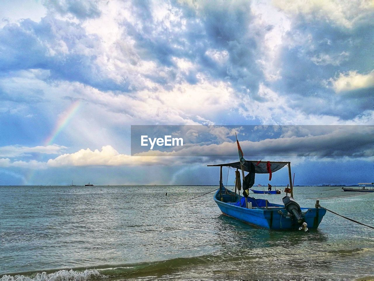 cloud - sky, sea, sky, nautical vessel, water, transportation, nature, day, horizon over water, scenics, mode of transport, beauty in nature, outdoors, real people, men, beach, one person, outrigger, people