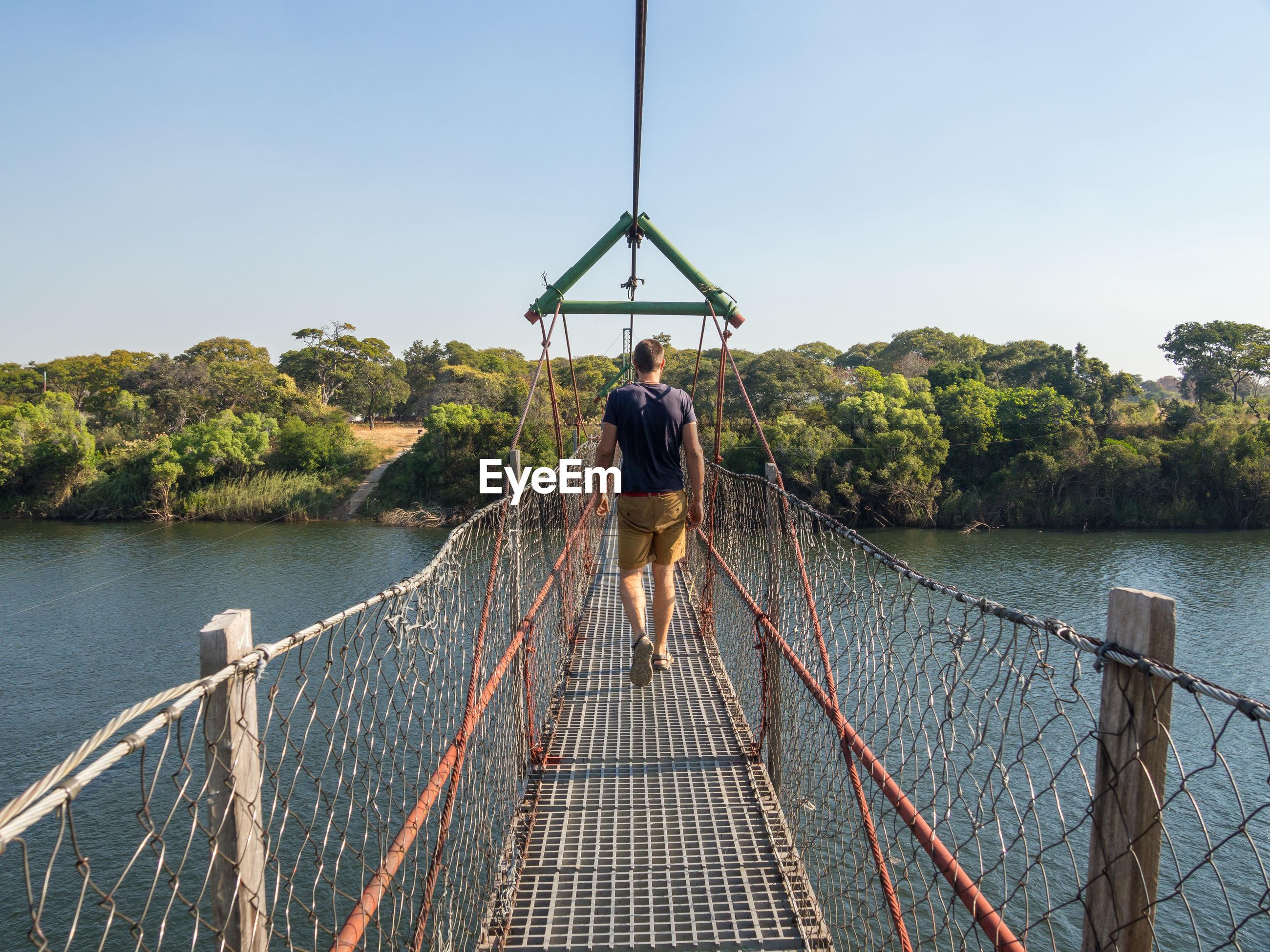 Rear view of man walking on footbridge over river zambezi, chinyingi, zambia
