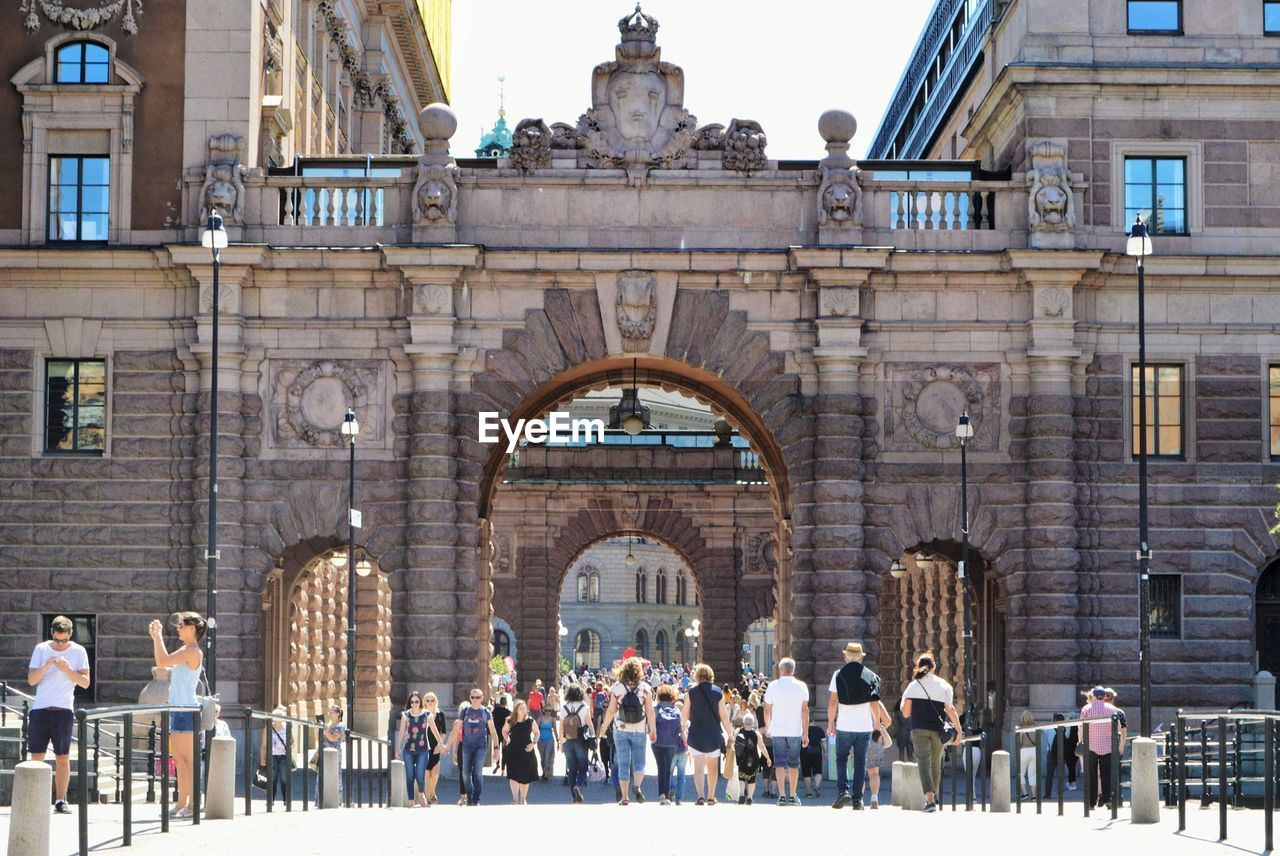 architecture, group of people, real people, crowd, built structure, large group of people, building exterior, men, the past, history, arch, women, day, adult, window, travel destinations, lifestyles, tourism, building, clock, visit