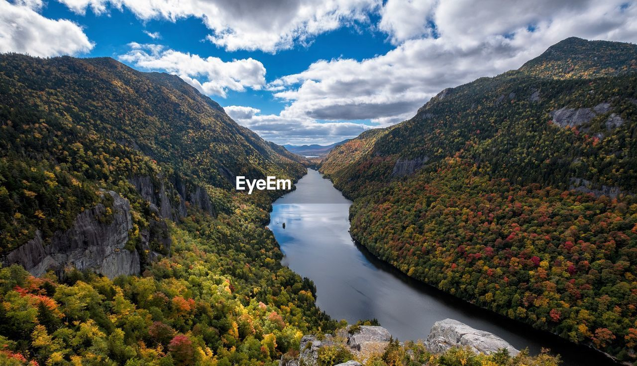Scenic view of river amidst tree mountains against sky during autumn