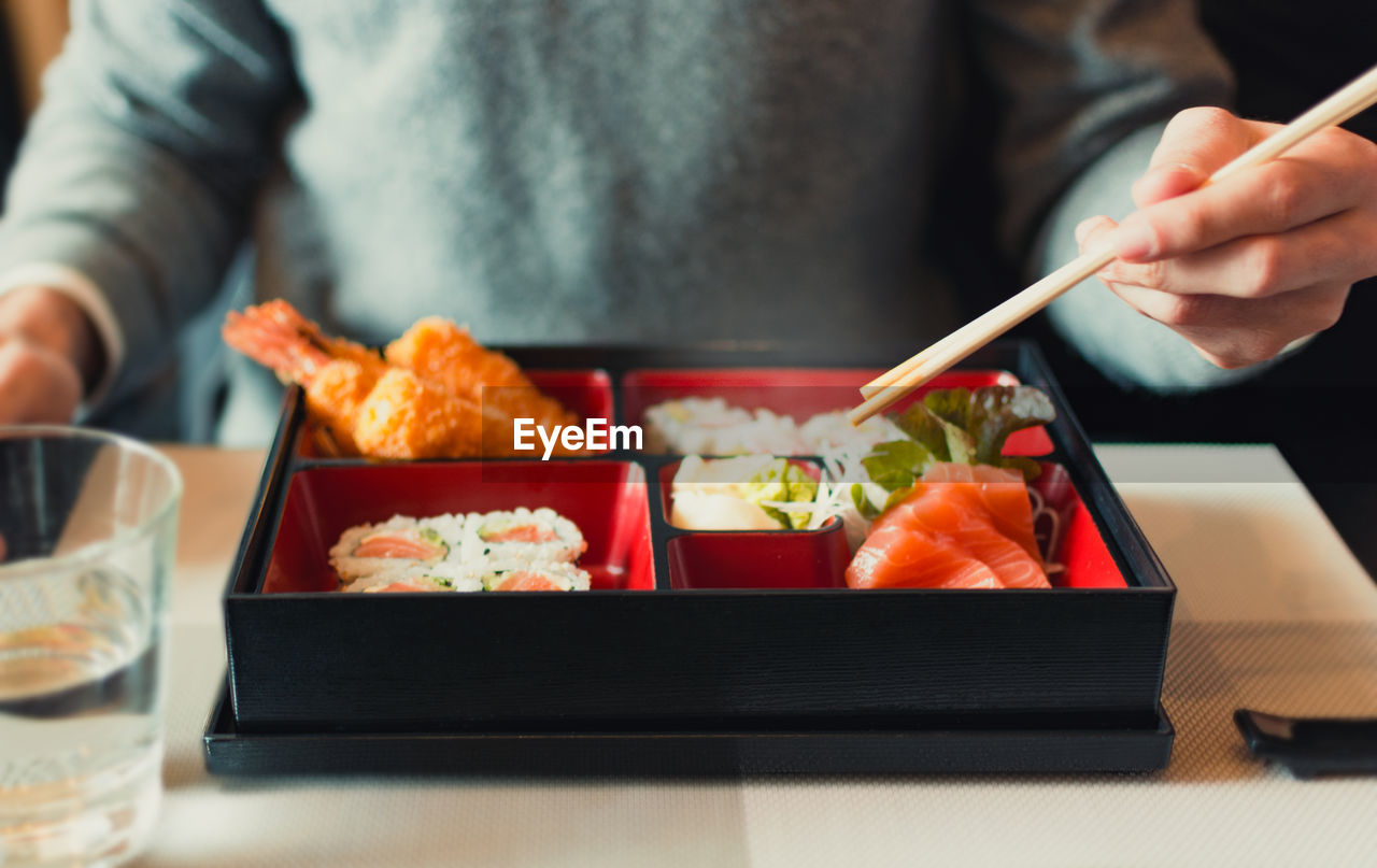 food and drink, food, human hand, one person, asian food, freshness, real people, japanese food, hand, human body part, holding, sushi, midsection, chopsticks, healthy eating, indoors, tray, table, preparation, preparing food