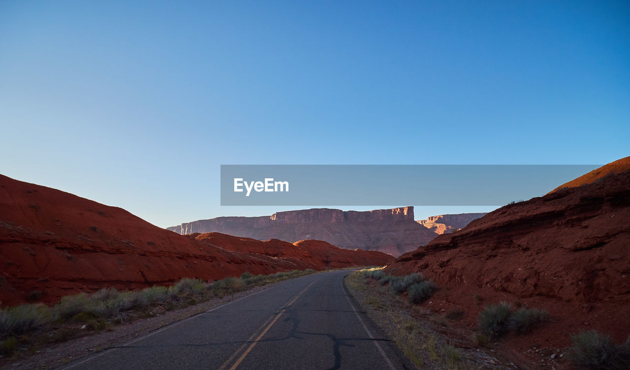 sky, direction, the way forward, road, mountain, clear sky, copy space, transportation, diminishing perspective, nature, landscape, scenics - nature, beauty in nature, environment, tranquil scene, day, blue, vanishing point, non-urban scene, tranquility, no people, mountain range, outdoors, arid climate, long, climate