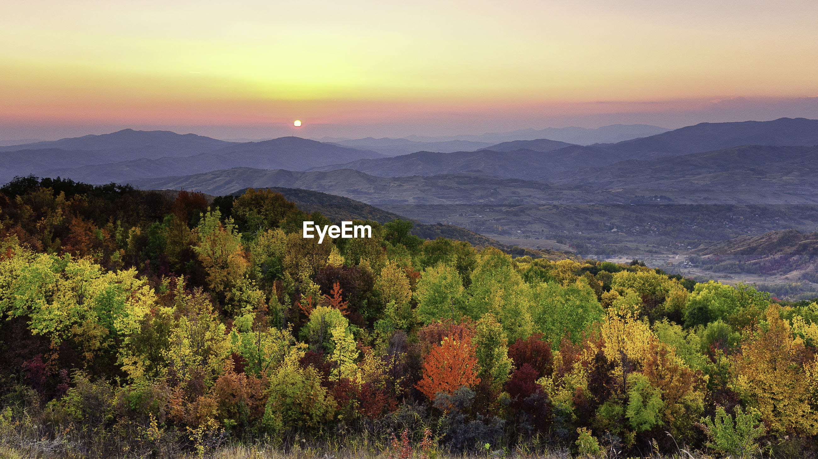 SCENIC VIEW OF TREES AND MOUNTAINS AGAINST SKY DURING SUNSET