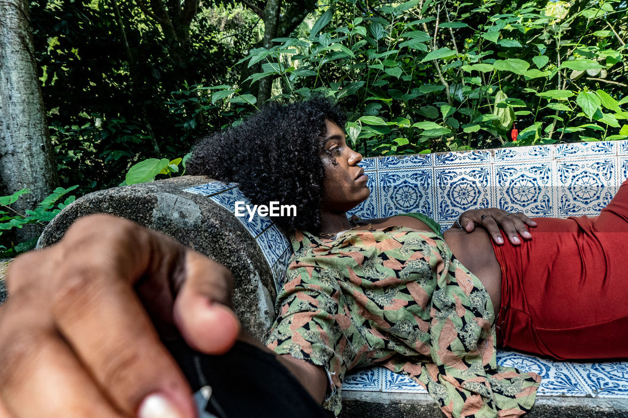 Woman lying on sofa in forest