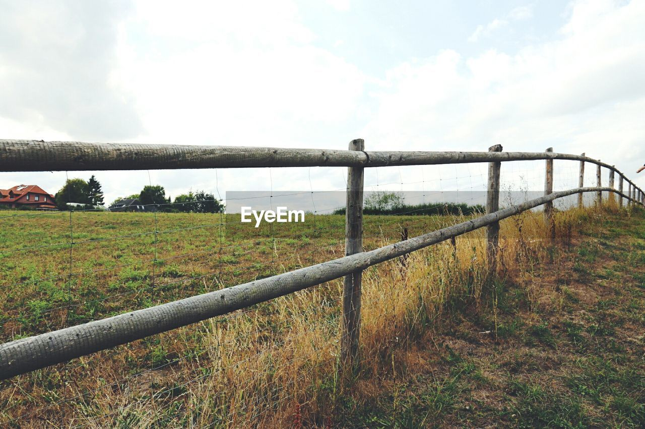 landscape, plant, land, sky, grass, field, nature, fence, barrier, boundary, security, tranquil scene, environment, no people, day, safety, protection, tranquility, scenics - nature, metal, outdoors