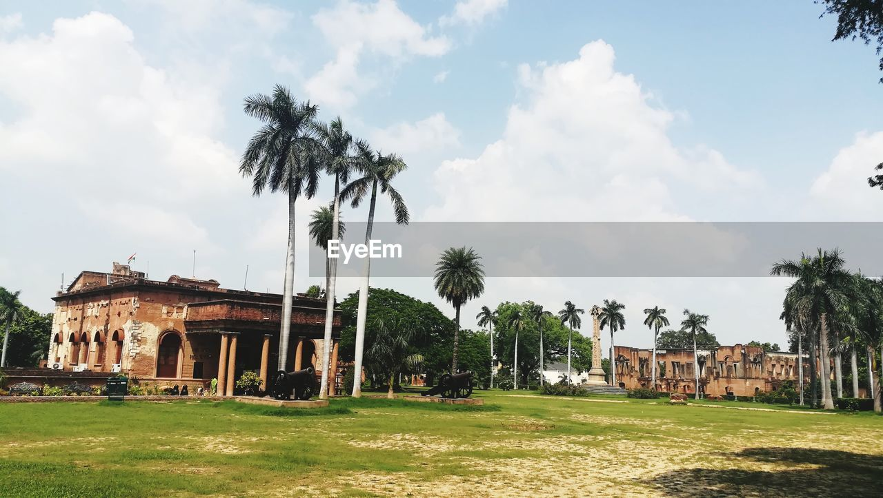 architecture, built structure, palm tree, building exterior, tree, old ruin, sky, cloud - sky, day, damaged, house, abandoned, outdoors, history, no people, grass