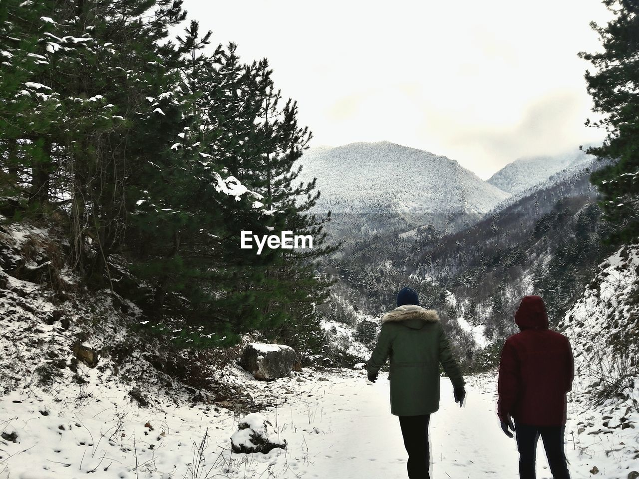 Rear View Of Two People Walking On Snow Covered Mountain During Winter