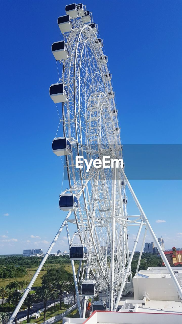 Low Angle View Of Ferries Wheel Against Blue Sky