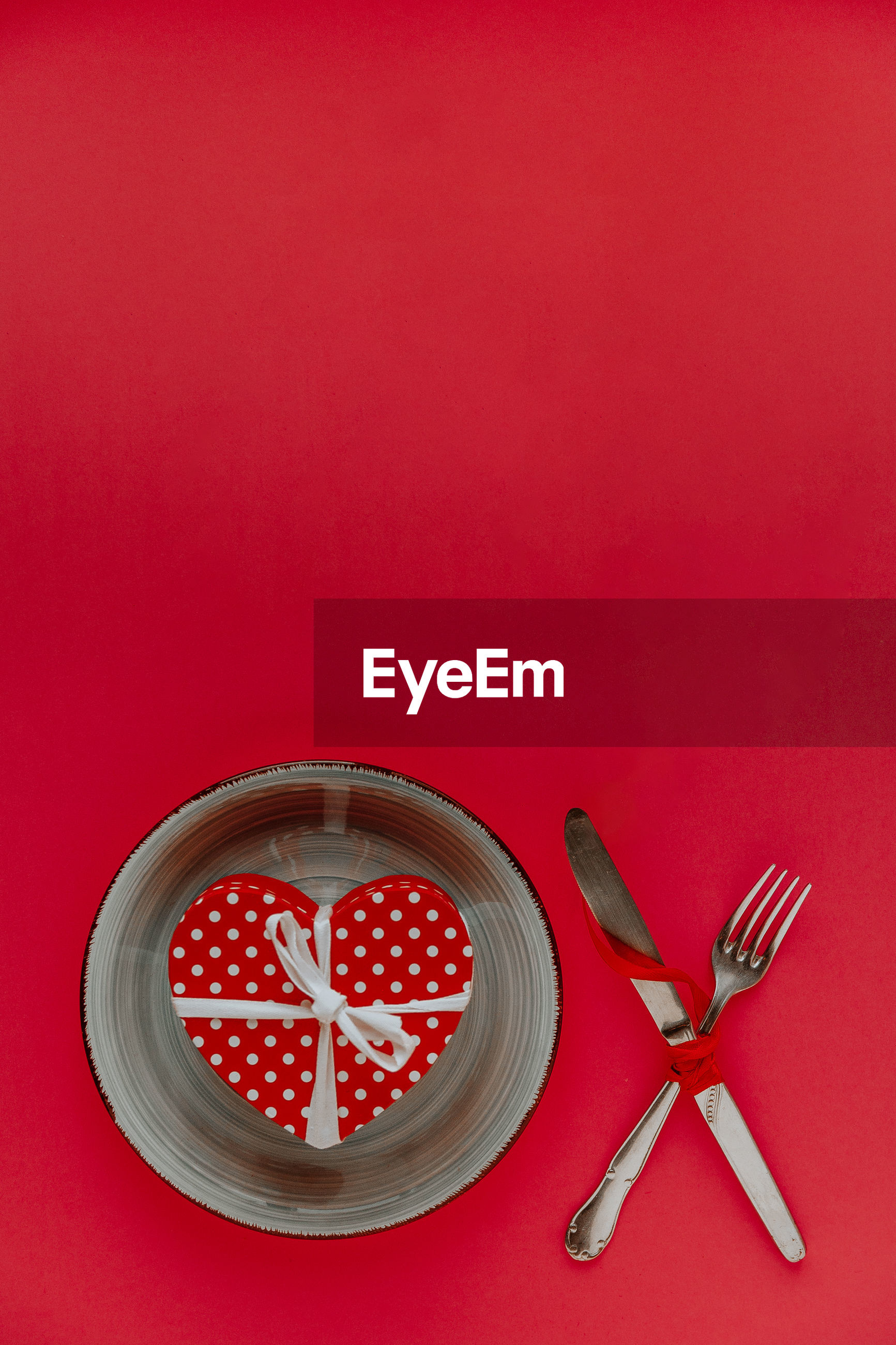 Directly above shot of heart shape in bowl with cutlery over red background