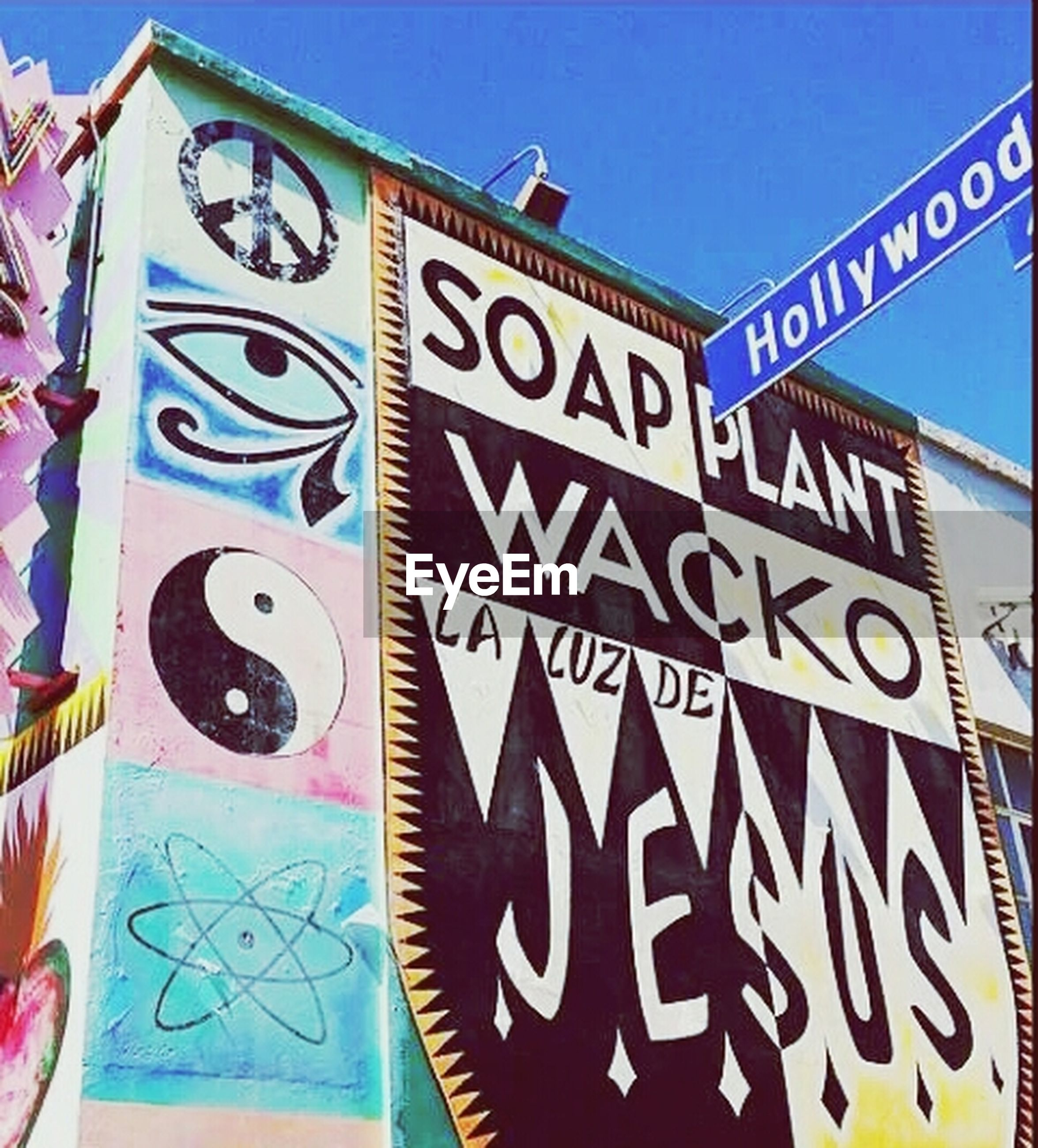 text, western script, communication, blue, low angle view, capital letter, architecture, built structure, non-western script, information, graffiti, clear sky, sign, art, information sign, building exterior, creativity, art and craft, wall - building feature, multi colored