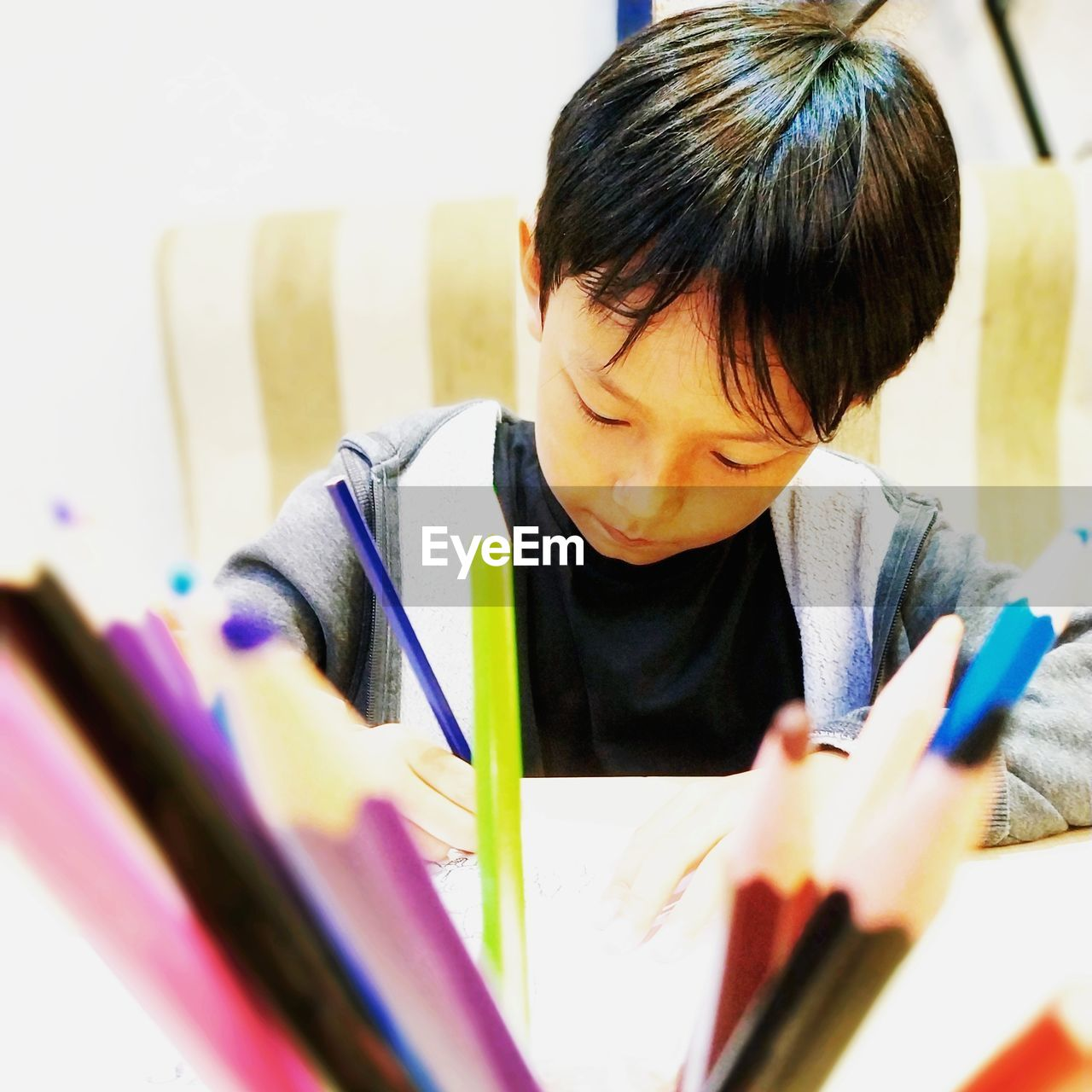 real people, one person, selective focus, child, indoors, book, holding, publication, headshot, childhood, lifestyles, boys, education, learning, paper, writing, leisure activity, studying, innocence, hairstyle