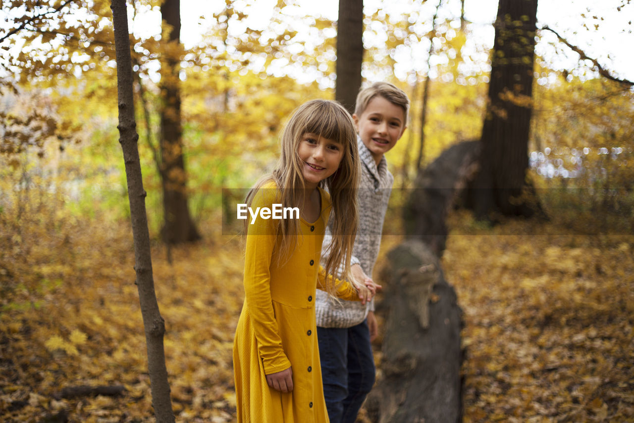 togetherness, smiling, two people, happiness, bonding, tree, leisure activity, emotion, women, casual clothing, land, young women, forest, plant, family, looking at camera, girls, young adult, three quarter length, yellow, hairstyle, hair, beautiful woman, sister, positive emotion, daughter, outdoors