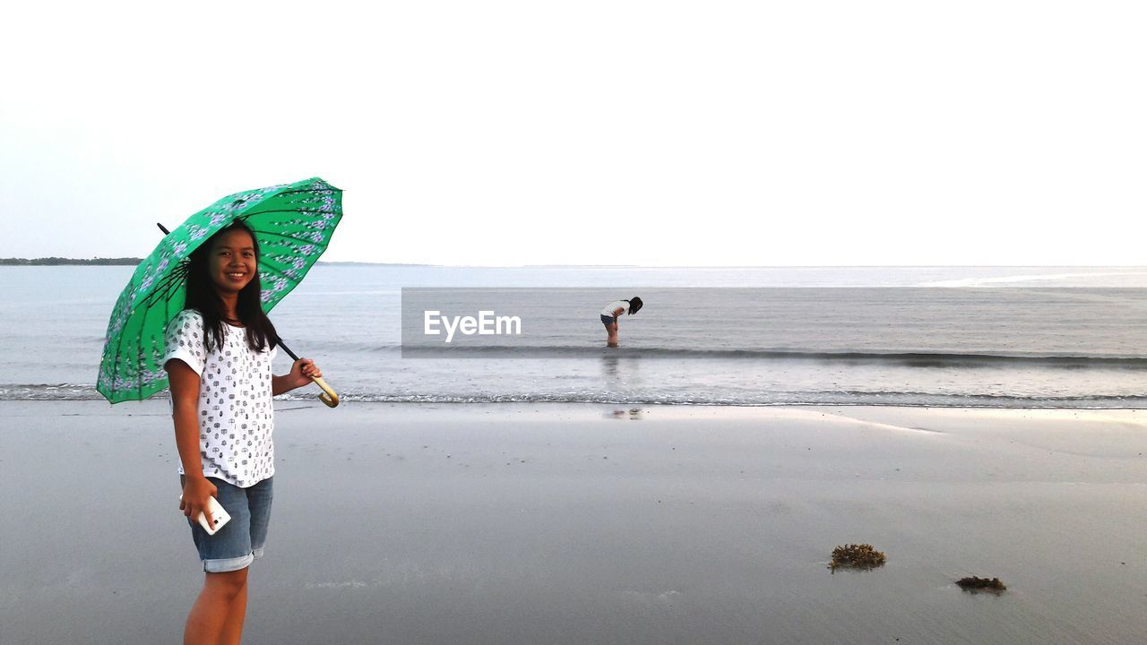 beach, sea, real people, horizon over water, water, shore, leisure activity, standing, sand, nature, lifestyles, scenics, young women, full length, one person, walking, sky, beauty in nature, vacations, day, young adult, clear sky, outdoors, women, ankle deep in water, portrait