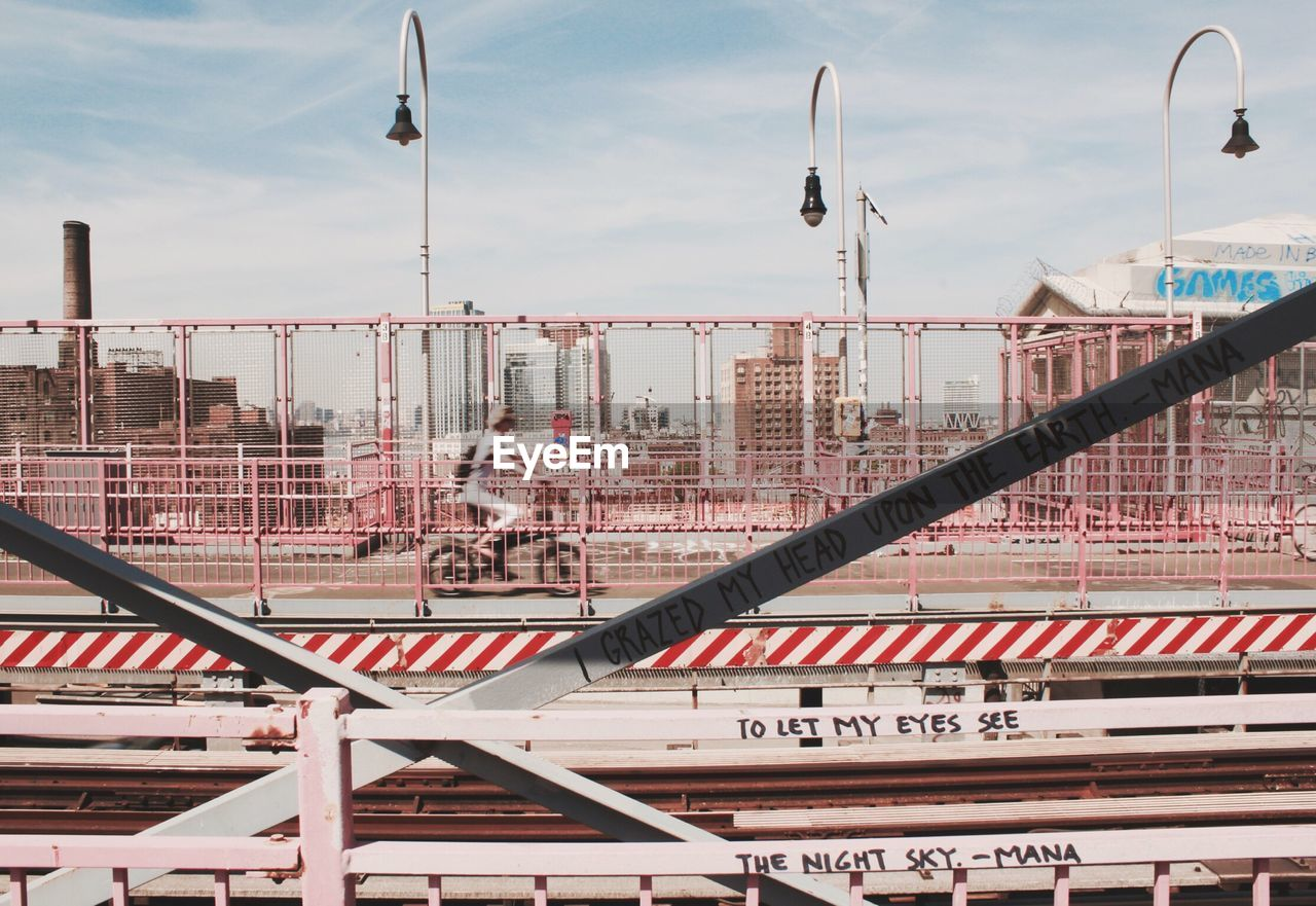 Woman Cycling Across Railroad Bridge