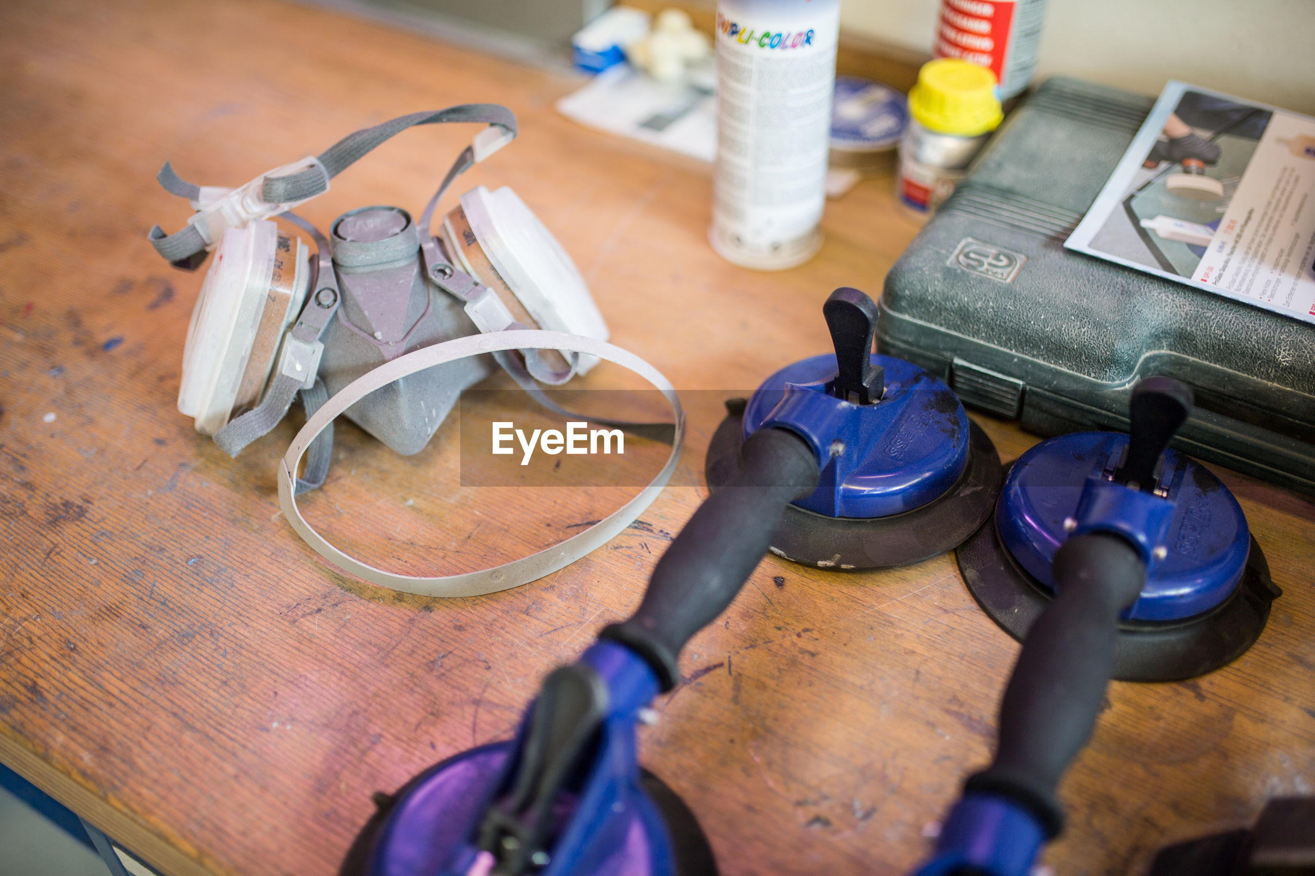 High angle view of gas mask and work tools on table