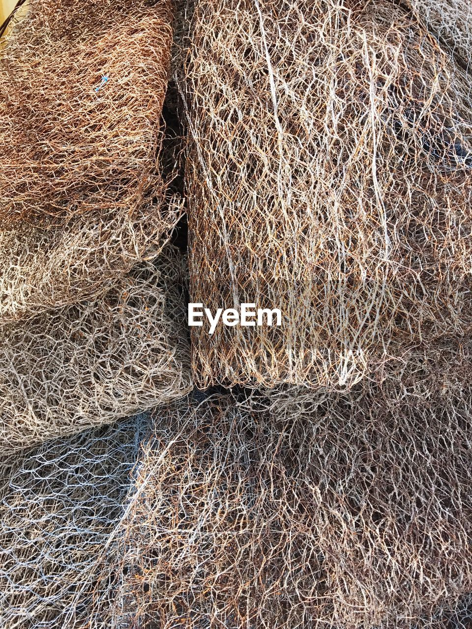 full frame, backgrounds, rolled up, fishing net, fishing equipment, stack, no people, outdoors, textured, fishing tackle, day, close-up, brown, hay bale