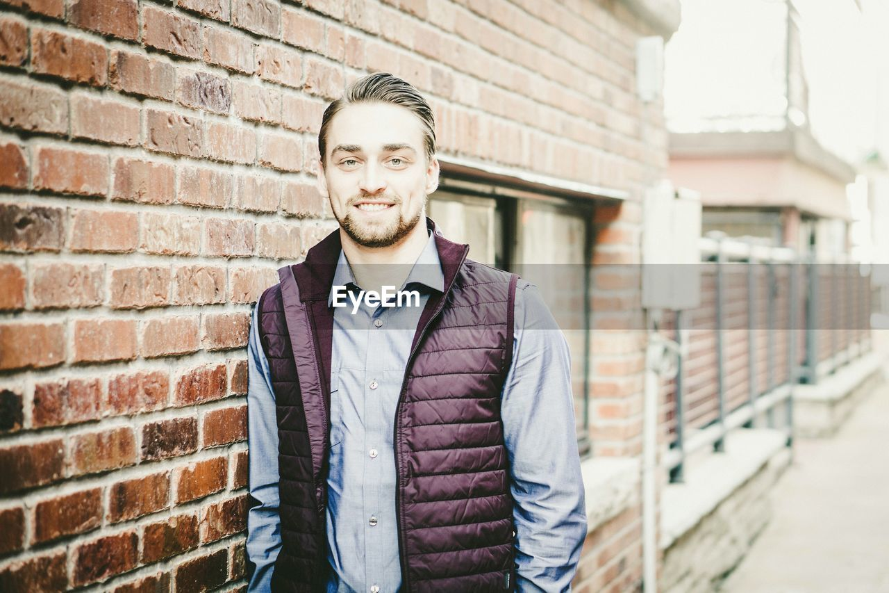 Portrait of smiling young man standing by brick wall