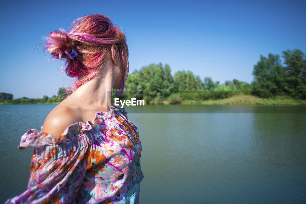 one person, water, hairstyle, hair, women, sky, lake, lifestyles, nature, beauty in nature, leisure activity, redhead, day, adult, real people, tranquil scene, focus on foreground, young adult, dyed hair, pink color, outdoors, beautiful woman