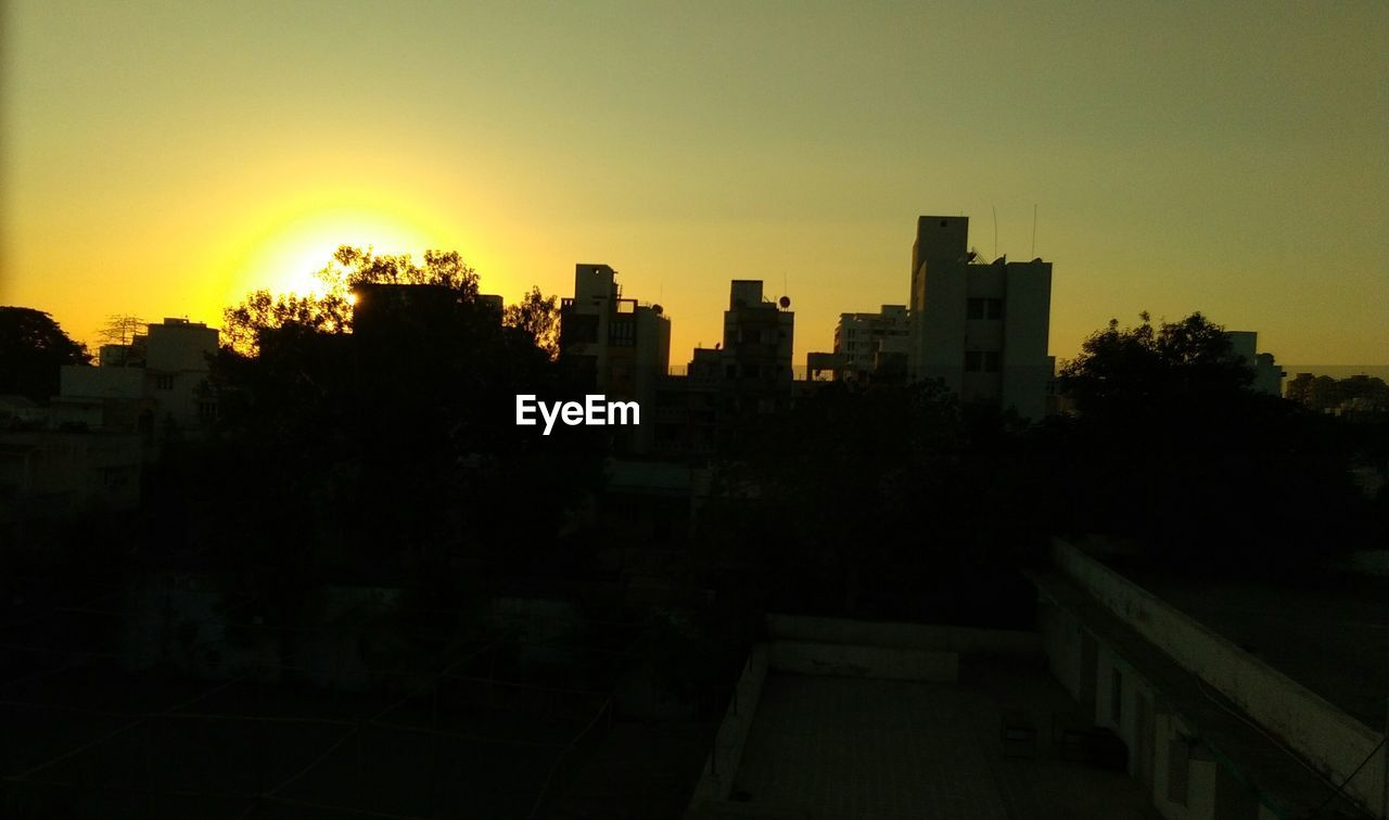 sunset, architecture, building exterior, city, cityscape, silhouette, built structure, no people, clear sky, tree, sky, skyscraper, outdoors, nature, residential, day