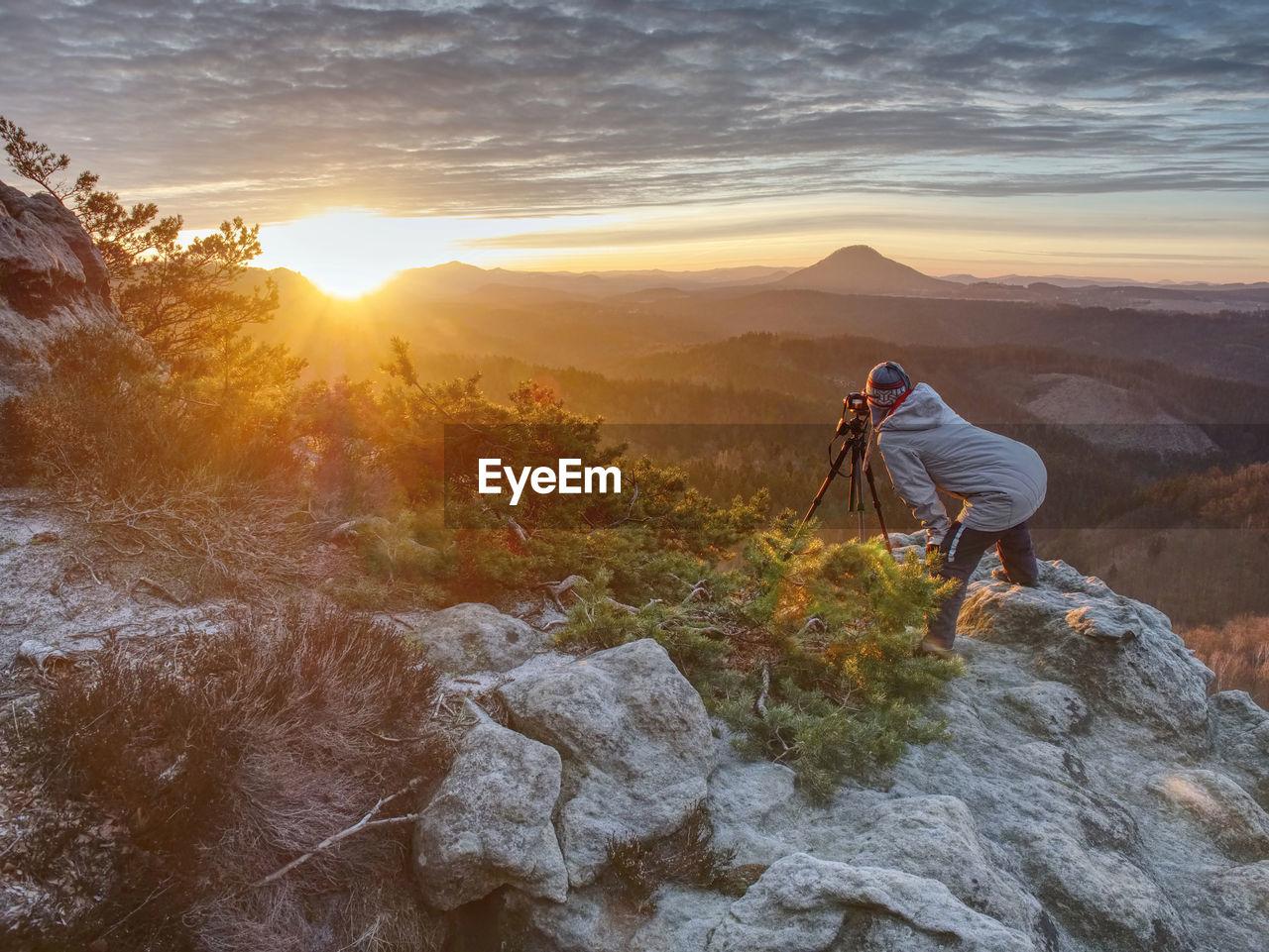 Woman art photographer works at camera on fiber glass tripod. misty spring daybreak above land